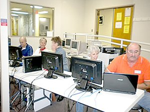 Photo submitted Volunteer Computer Club members work on devices brought in to their training center in the Highlands Crossing building.