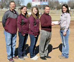 Westside Eagle Observer/RANDY MOLL Savannah Dickinson, vice president and branch manager of Farm Credit of Western Arkansas (right), presents a check to Brae Harper, Gentry High School principal and athletic director, for the purchase of a new scoreboard for the softball field in the Merrill Reynolds Memorial Complex at the high school on Friday. Dickinson and Harper were accompanied on the softball field by head softball coach Paul Ernest and assistant coaches Ayla Smartt and Erica Jones.