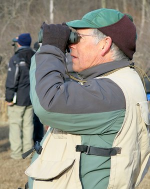 Westside Eagle Observer/RANDY MOLL Joe Neal, area bird expert, looks for wading birds in the mudflats along SWEPCO Lake on Saturday during a Northwest Arkansas Audubon Society fieldtrip to the Eagle Watch Nature Trail on Saturday morning (Feb. 3, 2018). About 40 people were out for the bird-watching event.