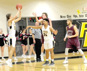 MARK HUMPHREY ENTERPRISE-LEADER Prairie Grove junior Will Pridmore utilizes a screen by teammate Demarkus Cooper to launch an open 3-pointer from the left corner. Prairie Grove defeated Lincoln, 64-36, Friday.