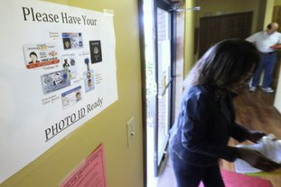 In this May 2014 file photo, an election worker walks past a voter ID sign at a Little Rock polling place. A lawsuit was filed Wednesday challenging the Arkansas Legislature's latest attempt to require that voters show photo identification before casting a ballot. (AP Photo/Danny Johnston, File)