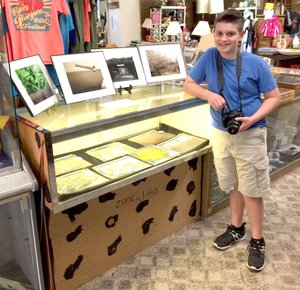 Courtesy photo Eleven-year-old Griffin Schutten showcases his talent at a local flea market vendor booth. The young entrepreneur and photographer has a real eye for capturing wildlife, flowers and an historical flooding event in Anderson.