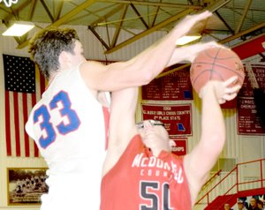 RICK PECK/SPECIAL TO MCDONALD COUNTY PRESS McDonald County's Tim Shields gets fouled by East Newton's Dustin McDermott during the Mustangs' 60-45 win on Feb. 2 at East Newton High School. Shields finished with a career-high 25 points to lead McDonald County.