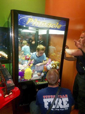 This photo made available by the Titusville Fire and Emergency services shows fire fighters attempting to rescue a boy who crawled inside a claw-style vending machine, Wednesday, Feb. 7, 2018, in Titusville, Fla. The boy sat atop the stuffed toys while firefighters took just 5 minutes to get him out.