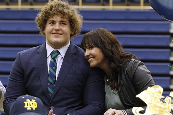 Pulaski Academy senior Luke Jones gets a hug from his mother, Terry, after signing to play football at Notre Dame on Wednesday, Feb. 7, 2018, in Little Rock. Jones, an offensive lineman, was one of 10 players who de-committed from Arkansas in the class of 2018.
