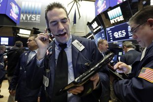 """Trader Gregory Rowe, center, works on the floor of the New York Stock Exchange on Friday. U.S. stocks wavered between small gains and losses in morning trading Friday, giving up some of a big jump that came right after the opening bell. The strong open came a day after the market entered a """"correction"""" for the first time in two years. (AP Photo/Richard Drew)"""