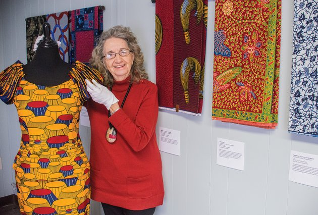 farrell-ford-executive-director-of-the-clark-county-arts-and-humanities-council-shows-one-of-the-highlights-of-the-traveling-art-exhibit-wandering-spirit-african-wax-prints-that-is-on-display-at-the-arkadelphia-arts-center-this-kings-chair-dress-form-created-in-1980-is-part-of-the-exhibit-courtesy-of-the-beatrice-benson-collection-visitors-to-the-exhibit-are-not-allowed-to-touch-the-fabrics-with-their-bare-hands-but-will-be-issued-gloves-similar-to-those-ford-is-wearing