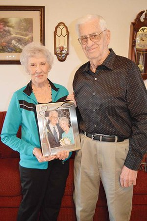 "Newlyweds Elsie and Jack Grimes of Guy hold an album of photos from their Sept. 23 wedding. They met on a blind date, arranged by a mutual friend, and were married four months later. They each had been happily married for more than 60 years, and their spouses died within nine days of each other. Matchmaker Donna Treece of Guy said, ""The first little date, they seemed very comfortable together. The next thing I know, they're getting married."""