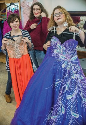 Arkadelphia Human Development Center resident Candie Jo Butler, center, shows a possible jewelry selection, while residents Kelsey Heffner, left, and Hannah White show possible ball-gown selections for Winter Wonderland Prom 2018. Formalwear for women and men, shoes, accessories, flowers, hairstyling and other services have been donated for Saturday's event.
