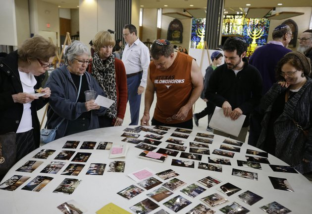 people-look-at-a-display-of-photos-during-a-final-service-held-at-united-orthodox-synagogues-in-houston-as-part-of-a-farewell-event-the-building-was-damaged-by-three-recent-fl-oods-that-occurred-on-memorial-day-2015-on-tax-day-2016-and-the-fl-oods-caused-by-hurricane-harvey-in-august-last-year
