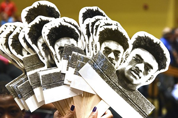 The family of five-star cornerback Patrick Surtain Jr., a defensive back from the football team at American Heritage High School, holds up photos of him on a stick on national signing day, Wednesday, Feb. 7, 2018, in Plantation, Fla. (Taimy Alvarez/South Florida Sun-Sentinel via AP)