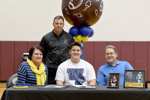 Bud Sullins/Special to Siloam Sunday Siloam Springs senior Isaac Knudsen signed Wednesday to play football at William Penn University in Oskaloosa, Iowa. Pictured are: Front from left, mother Sena Knudsen, Isaac Knudsen, father Bruce Knudsen and former Siloam Springs head football coach Bryan Ross, back.