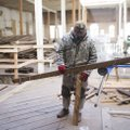 Hugo Rodriguez of Wilson Flooring measures wood panels for flooring Thursday at the old Dollar Saver...