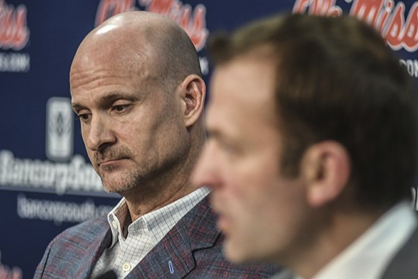 Mississippi head coach Andy Kennedy, left, listens as athletic director Ross Bjork speaks at a press conference at the Pavilion at Ole Miss in Oxford, Miss. on Monday, February 12, 2018. Kennedy, in his 12th season as Mississippi head coach, announced he would not return as coach following this season. (Bruce Newman, Oxford Eagle via AP)