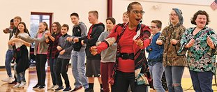The Sentinel-Record/Grace Brown PERFORMANCE READY: Professional storyteller Linda Gorham dances with students in the Lake Hamilton Middle School gym during her performance about the Little Rock Nine on Monday.