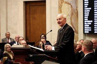 The Associated Press HUTCHINSON SPEAKS: Arkansas Gov. Asa Hutchinson speaks to a joint session of legislators, Monday at the state Capitol in Little Rock, Ark. The governor told lawmakers that, next year, he would like them to cut the state's top income tax rate from 6.9 percent to 6 percent, a move that would save Arkansas' top earners $180 million annually.