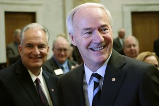 Gov. Asa Hutchinson prepares to speak to a joint session of legislators Monday at the state Capitol in Little Rock. Behind him is Arkansas Treasurer Dennis Milligan. The governor told lawmakers that, next year, he would like them to cut the state's top income tax rate from 6.9 percent to 6 percent, a move that would save Arkansas' top earners $180 million annually. (AP Photo/Kelly P. Kissel)