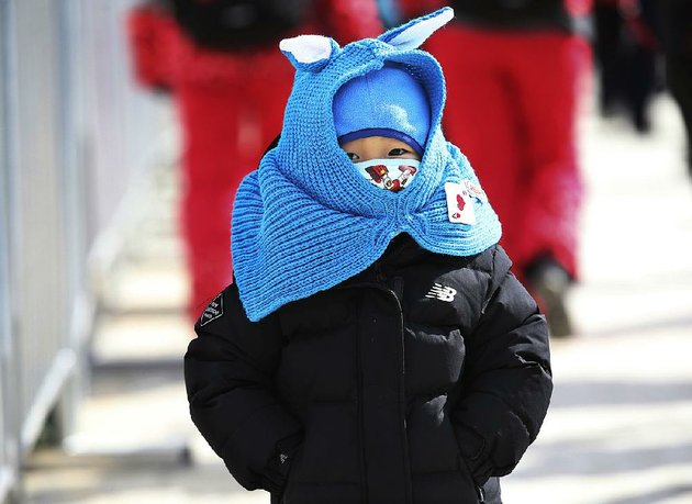a-bundled-up-girl-walks-near-phoenix-snow-park-at-the-winter-olympics-colder-than-normal-temperatures-and-strong-winds-have-caused-problems-for-spectators-and-competitors