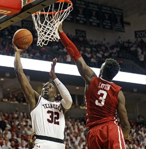 Texas Tech's Norense Odiase (32) shoots a layup in front of Oklahoma's Kadeem Lattin on Tuesday during the No. 7 Red Raiders' 88-78 victory over the No. 23 Sooners in Lubbock, Texas.