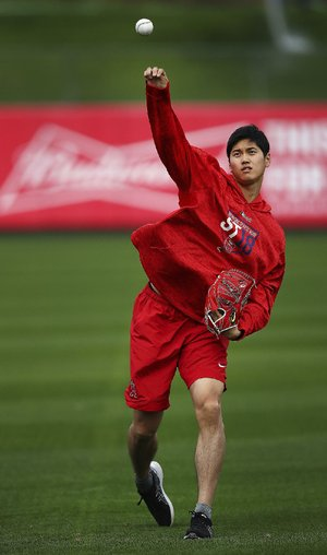 Shohei Ohtani of the Los Angeles Angels throws during a spring training workout Tuesday in Tempe, Ariz. The 23-year-old Japanese standout, who signed with the Angels two months ago, is getting looks both as a pitcher and as an outfielder.