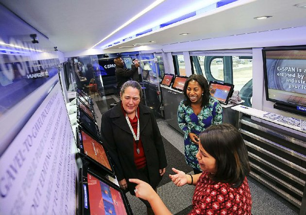 jenae-green-top-right-and-vanessa-torres-bottom-of-c-span-show-visitor-michelle-gibson-some-of-the-interactive-features-aboard-the-c-span-tour-bus-during-its-stop-tuesday-at-the-state-capitol