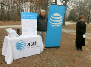 Westside Eagle Observer/SUSAN HOLLAND Cathy Foraker, AT&T director of external affairs (right), announces expanded high-speed Internet access to rural areas of Benton County. Ron Anderson, area manager for planning and engineering, displays an information board showing how the AT&T Fixed Wireless Internet system works. The announcement was made Tuesday afternoon, Feb. 6, in the parking lot at the Mount Pleasant Missionary Baptist Church.