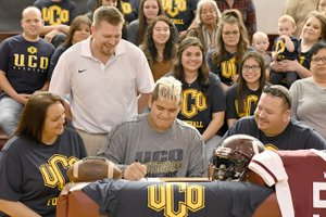 """Bud Sullins/Special to the Herald-Leader Oaks-Mission (Okla.) senior lineman Joseph """"Choogie"""" Young signed a letter of intent Friday to play football at the University of Central Oklahoma in the Oaks gymnasium. Also pictured are his mother Penny, left, and father Chero, right, Oaks head football coach C.D. Thompson, standing, and a host of friends and family."""