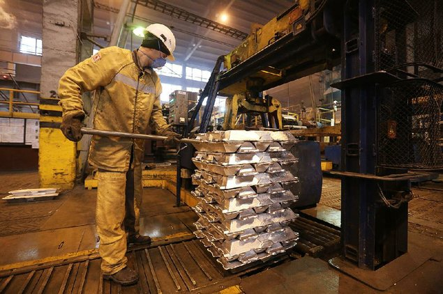 A worker at a foundry in Krasnoyarsk Russia positions aluminum ingots before binding them for shipping