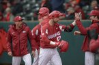 Arkansas designated hitter Luke Bonfield (center) wears a Hog hat after hitting a three-run home run against Bucknell Saturday, Feb. 17, 2018, during the first inning at Baum Stadium in Fayetteville.