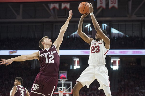 Arkansas guard C.J. Jones shoots over Texas A&M defender Chris Collins during a game Saturday, Feb. 17, 2018, in Fayetteville.
