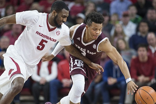 Arkansas' Arlando Cook (5) and Texas A&M's Admon Gilder (3) go for a loose ball during the first half of a game Saturday, Feb. 17, 2018, in Fayetteville.