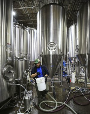 Jerry Gorman cleans fermenting tanks Wednesday at Lost Forty Brewing, where two new 90-barrel fermenters will help produce more specialty beers.
