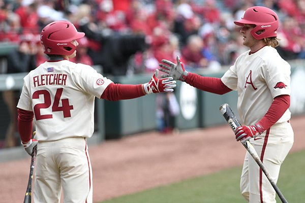 Arkansas outfielder Dominic Fletcher (24) congratulates catcher Grant Koch during a game against Bucknell on Sunday, Feb. 18, 2018, in Fayetteville.