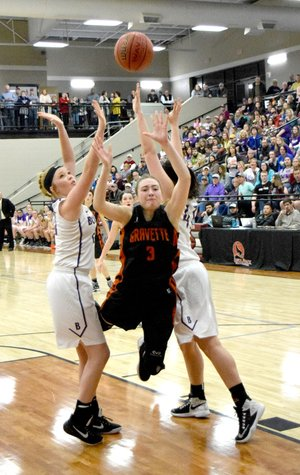 Westside Eagle Observer/MIKE ECKELS Kyrstin Branscum (Gravette 3) loses her balance as she tries to drive between two Berryville players during the championship round of the 1 4A Northwest Conference tournament at Lincoln High School Feb. 17.
