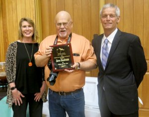 Westside Eagle Observer/SUSAN HOLLAND Steve Huckriede (center), displays the plaque he received honoring him as Gravette Citizen of the Year at the Greater Gravette Chamber of Commerce banquet Thursday, Feb. 15. Steve, who operates Steve Huckriede Photography, is serving his second term as GGCC secretary. He is pictured with Sundee Hendren, Chamber treasurer, and Fred Overstreet, Chamber president.