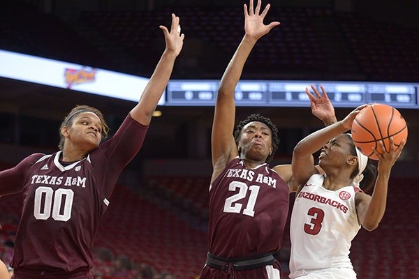 Arkansas' Malica Monk (3) attempts a shot in the lane as Texas A&M's Jasmine Lumpkin (21) and Khaalia Hillsman (00) defend Thursday, Feb. 22, 2018, during the second half in Bud Walton Arena.