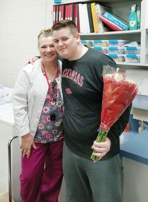 "Rose Bud sophomore Joey Coughlin brings flowers to Jeannie Cook, the district's school nurse, a week after she helped save his life after he collapsed in a classroom. Cook said Coughlin had no pulse, and she performed CPR on him and used an automatic external defibrillator until first responders arrived. Coughlin is back at school and ""looks great,"" Cook said."