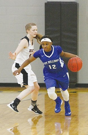 Terrance Armstard/News-Times Strong's Dynasty Davis (12) goes around Hermitage's Haley Raney (10) during the first half of their game at the 5-1A Regional Tournament in Hampton Friday. The Lady Bulldogs upended Hermitage 46-44 to advance to the finals.