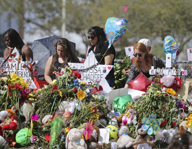 mourners-bring-flowers-as-they-pay-tribute-at-a-memorial-for-the-victims-of-the-shooting-at-marjory-stoneman-douglas-high-school-on-sunday-feb-25-2018-in-parkland-fla-david-santiagomiami-herald-via-ap