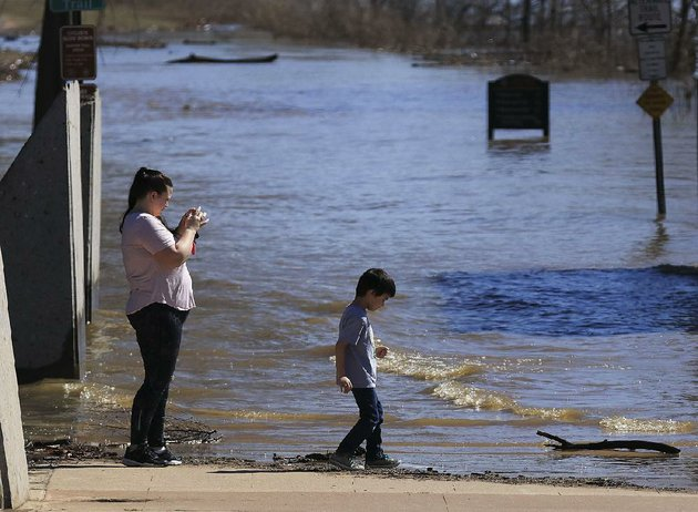 kelli-fletcher-and-her-son-gabriel-gomez-6-look-at-the-floodwater-covering-the-arkansas-river-trail-at-the-foot-of-the-big-dam-bridge-on-monday-afternoon-in-north-little-rock-the-surging-arkansas-river-has-overflowed-part-of-the-trail-and-more-rain-is-expected-in-little-rock-in-the-coming-days