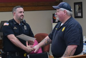 Westside Eagle Observer/MIKE ECKELS Officer Randy Deason, Decatur Police Department, receives congratulations from Chief Joe Savage during the Decatur City Council meeting at Decatur City Hall Feb. 15. Deason received a commendation for saving the life of a three-month-old baby who was choking and unresponsive Jan. 2.