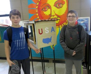 Westside Eagle Observer/SUSAN HOLLAND Eighth grader Jaxon Galyean and seventh grader Matthew Holland, students in Pam Page's gifted and talented classes, pose beside the Little Free Library they helped construct. Students chose the themes and built the structures which will be delivered to provide books in areas of south Arkansas with few libraries.
