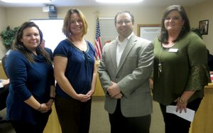 Westside Eagle Observer/SUSAN HOLLAND Gravette teachers Neka Lunderquist (left) and Stacy Bingham receive a check from Alan Rutledge, board president of Autism Involves Me, and Paula Towle, AIM executive director. The $750 AIM2EDUCATE Grant check will be used to purchase sensory equipment for their classrooms.