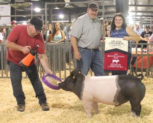 Westside Eagle Observer/SUBMITTED Paige Barrett (right) receives a Grand Champion banner from judge Brian Anderson (center) after winning the Benton County Youth Livestock show's Grand Champion Market hog award at the Benton County Fair in Bentonville Aug. 11, 2017.