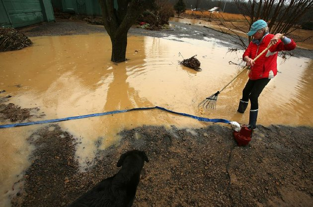 sandy-wilson-rakes-up-debris-wednesday-before-pumping-out-her-yard-in-pangburn-after-a-pond-levee-broke-and-sent-water-rushing-past-her-house-and-into-the-little-red-river-she-said-much-of-the-damage-was-in-the-garage-where-the-water-left-behind-a-couple-of-feet-of-mud