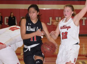 RICK PECK/SPECIAL TO MCDONALD COUNTY PRESS McDonald County's Rita Santillan splits Carl Junction's Megan Scott (42) and Shila Winder (12) on her way to the basket during the Lady Mustangs' 51-23 loss on Feb. 22 at Carl Junction High School.