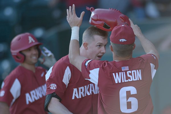 Arkansas left fielder Heston Kjerstad (center) is given the Hog hat by Hunter Wilson after Kjerstad hit a three-run home run against Dayton Thursday, March 1, 2018, during the fifth inning at Baum Stadium in Fayetteville.