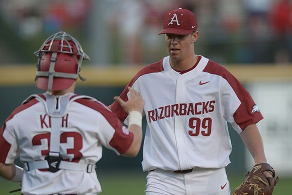 Arkansas pitcher Jackson Rutledge (99) is congratulated by catcher Grant Koch after recording the final out of a game against Southern Cal on Friday, March 2, 2018, in Fayetteville.
