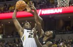 Missouri's Jeremiah Tilmon, left, shoots over Arkansas' Adrio Bailey, right, during the second half of an NCAA college basketball game Saturday, March 3, 2018, in Columbia, Mo. (AP Photo/L.G. Patterson)