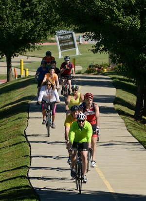 Riders make their way through Rogers during a Square to Square Bicycle Fun Ride on the Razorback Regional Greenway.